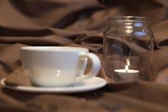 有一个茶碟的白色杯子在棕色背景 在玻璃烛台的灼烧的蜡烛 免版税库存照片