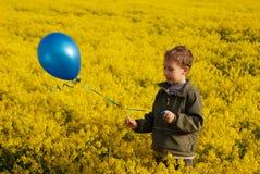 有一个蓝色气球的男孩在一个黄色领域 库存图片