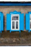 有一个蓝色窗口的老破裂的水泥墙壁与 图库摄影