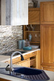 有一个蓝色水槽的木土气厨房 免版税库存图片