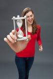 有一个蛋定时器的嬉戏的少妇在过大的手上 免版税图库摄影