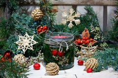 有一个蜡烛的一个瓶子,围拢由圣诞节装饰 库存照片