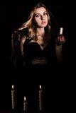 有一个蜡烛的害怕的少妇 库存图片