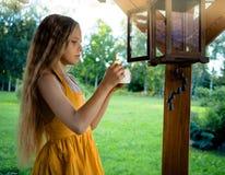 有一个蜡烛的小逗人喜爱的白肤金发的女孩和一个庭院灯笼在庭院里 免版税图库摄影