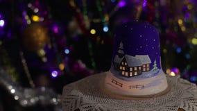 有一个蜡烛的新年的灯在一棵装饰的圣诞树的背景与淡光一本发光的诗歌选的 股票录像
