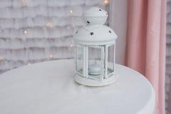 有一个蜡烛的白色灯笼里面在一张白色桌布 有装饰星的烛台 免版税库存图片