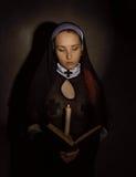有一个蜡烛的美丽的尼姑读圣经的 宗教概念 免版税图库摄影