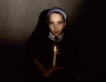 有一个蜡烛的美丽的尼姑读圣经的 宗教概念 免版税库存图片