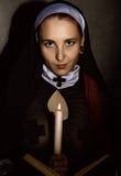 有一个蜡烛的美丽的尼姑读圣经的 宗教概念 图库摄影