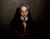 有一个蜡烛的美丽的尼姑读圣经的 宗教概念 免版税库存照片