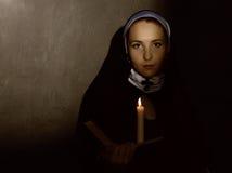 有一个蜡烛的美丽的尼姑读圣经的 宗教概念 库存照片