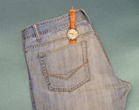 有一个表袋的青年牛仔裤在蓝色背景 库存图片