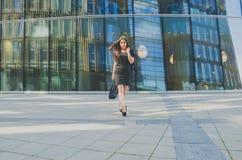 有一个袋子的企业女孩在手中在商业中心的背景 图库摄影