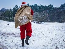 有一个袋子的圣诞老人与在积雪的领域的礼物 图库摄影