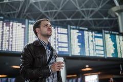 有一个袋子的年轻人在拿着咖啡的飞行时间表附近的机场 免版税库存照片