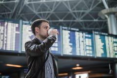 有一个袋子的年轻人在飞行时间表饮用的咖啡附近的机场 免版税库存图片