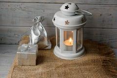 有一个被点燃的蜡烛的白色灯笼在礼物盒旁边 免版税库存照片