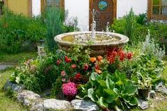 有一个装饰喷泉的花瓶在庭院里 库存图片