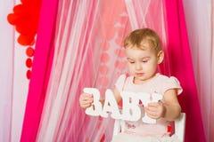 有一个词婴孩的小女孩桃红色裙子的 库存照片
