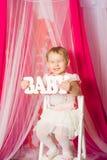 有一个词婴孩的小女孩桃红色裙子的 免版税库存图片