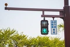 有一个走的人标志的一个绿色红绿灯允许人横跨路走 图库摄影