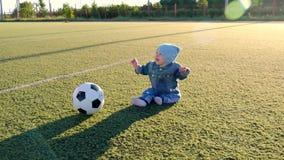有一个足球的微笑的男婴在橄榄球场 坐在有球的体育场的一个小孩的画象 远期 影视素材