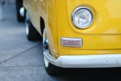 有一个车灯的黄色公共汽车 免版税库存图片