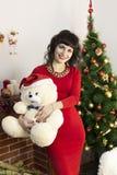 有一个软的玩具和一条大狗的一个女孩圣诞节的 免版税库存图片
