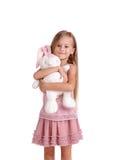 有一个软的玩具的一个英俊的小女孩,隔绝在白色背景 拥抱兔子玩具的一个逗人喜爱的孩子 复制空间 免版税库存照片