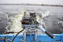 有一个连续老马达的一条老小船在河航行 库存图片