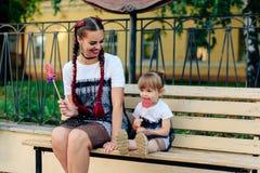 有一个逗人喜爱的女儿的愉快的年轻母亲与一个棒棒糖的一条长凳的在相同礼服的手上 免版税库存照片