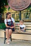 有一个逗人喜爱的女儿的愉快的年轻母亲与一个棒棒糖的一条长凳的在相同礼服的手上 库存图片