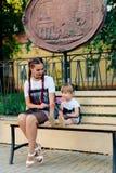有一个逗人喜爱的女儿的愉快的年轻母亲与一个棒棒糖的一条长凳的在相同礼服的手上 免版税库存图片