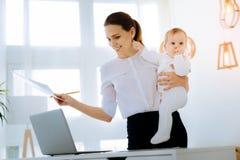 有一个逗人喜爱的婴孩的快乐的少妇她的胳膊的 库存图片