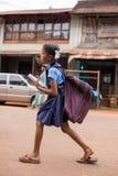 有一个重的书包的未认出的印地安女孩上学 免版税库存图片