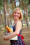 有一个野餐篮子的愉快的妇女在夏天户外 库存照片