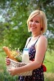 有一个野餐篮子的愉快的妇女在夏天 库存照片
