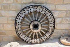 有一个金属外缘的老,古老木轮子,以一个石墙为背景 免版税库存照片