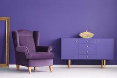 有一个金黄花瓶、轻松的扶手椅子和框架的紫色内阁在a 库存图片
