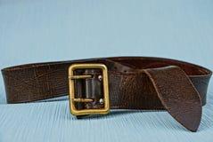 有一个铜扣的布朗传送带在一张蓝色桌上 图库摄影