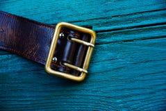 有一个铜扣的布朗皮带在绿色委员会 免版税图库摄影