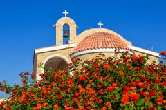 有一个铺磁砖的屋顶和响铃的东正教 在前景的英国兰开斯特家族族徽 塞浦路斯 Ayianapa 圣突然显现教会  免版税库存图片