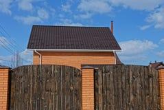 有一个铺磁砖的屋顶的私有砖房子在棕色木篱芭后 免版税库存照片