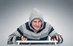 有一个键盘的滑稽的人在计算机前面 免版税库存图片