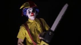 有一个锯的可怕小丑在黑暗 威胁您的小丑凶手 股票录像