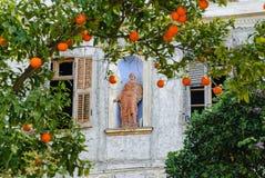 有一个雕象的一个老房子在与一棵橘树的一个门面在前景 库存照片
