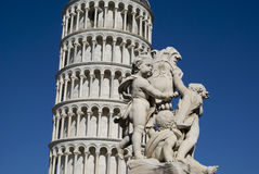 有一个雕象的比萨斜塔在前景 图库摄影