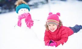 有一个雪人的愉快的儿童女孩在冬天步行 免版税库存图片