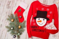 有一个雪人的红色毛线衣在木背景 与圣诞节装饰的毛皮树分支 免版税库存图片