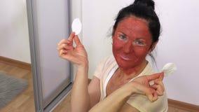 有一个面具的愉快的妇女从在她的面孔的黏土 股票录像